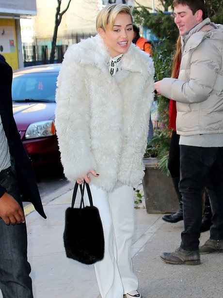 Miley Cyris wearing a fur coat