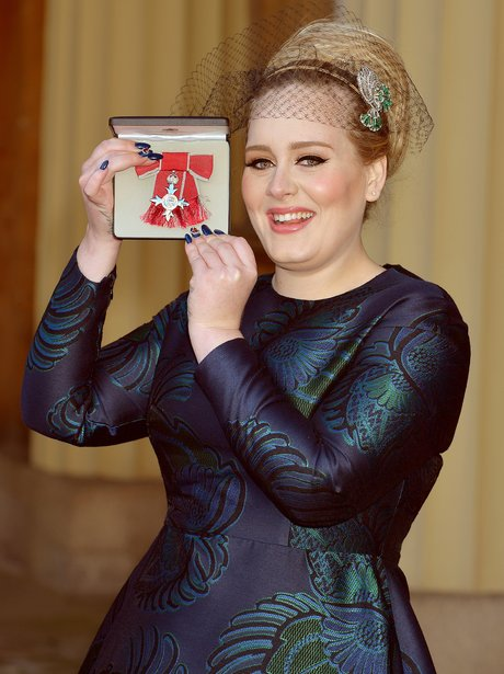 Adele holds up her MBE award
