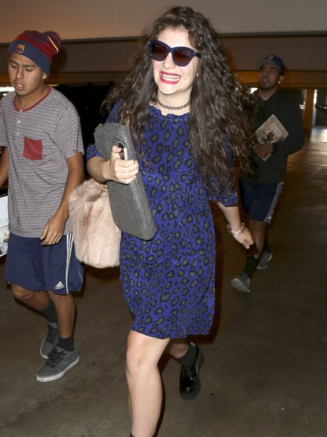 Lorde smiling at the airport