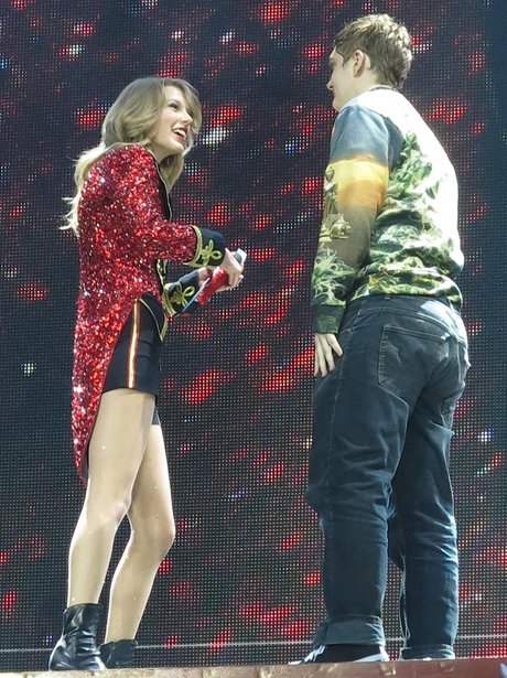 A fan joins Taylor Swift on stage