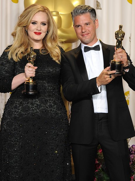 Adele and Paul Epworth hold up their awards