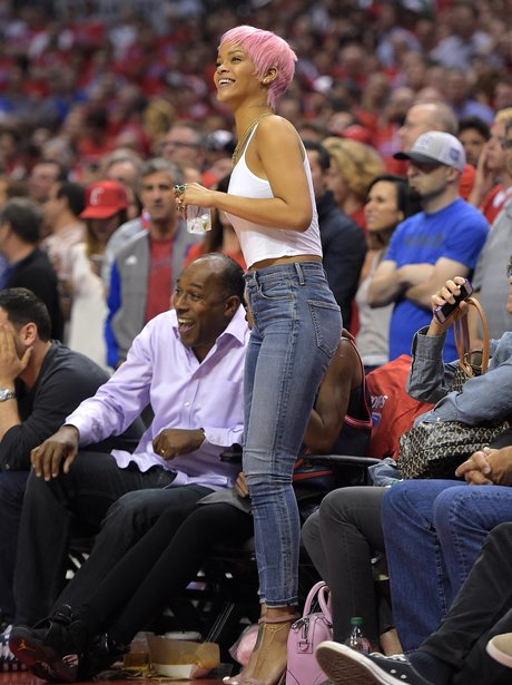 Rihanna wearing a pink wig watching basketball