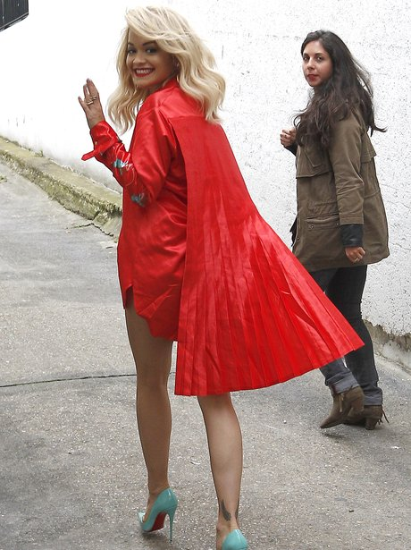 Rita Ora wearing a red cape