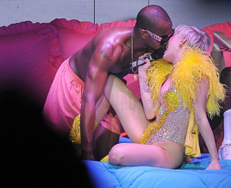 Miley Cyrus kisses a dancer on stag