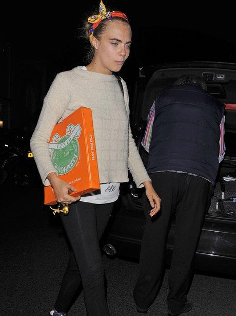 Cara Delevingne carrying a pizza