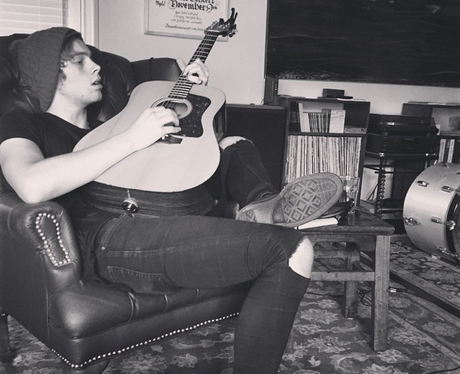 Luke form 5SOS paying a guitar
