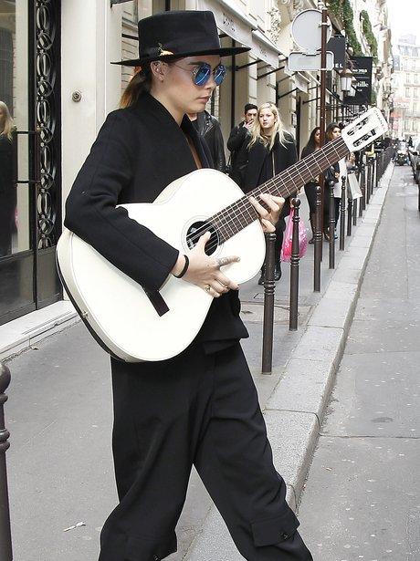 Cara Delevingne playig a guitar