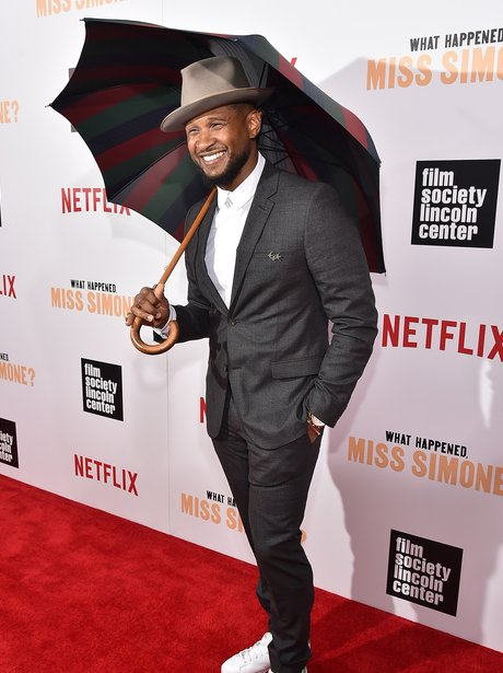 Usher hols an Umbrella on the red carpet