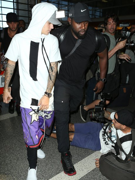 Justin Bieber looking at a paparazzi who's fallen