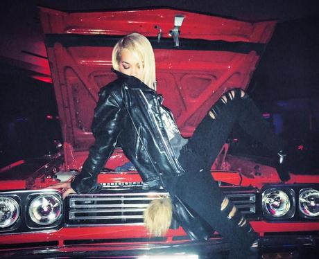 Rita Ora poses on a car bonnet