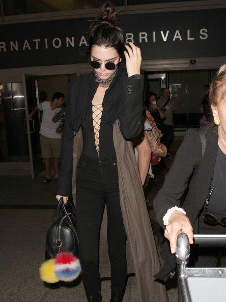 Kendall Jenner lands back in LA in plunging bodysu