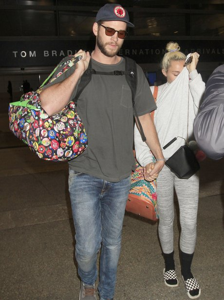 Miley Cyrus and Liam Hemsworth hold hands as they