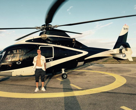 Justin Bieber infront of a helicopter