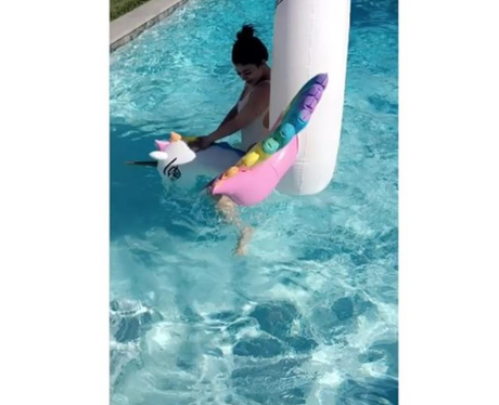 Kylie Jenner plays about in the pool