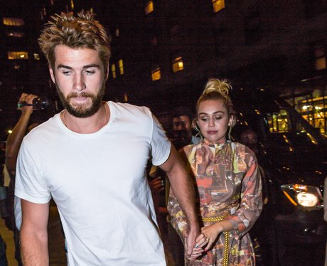 Miley Cyrus holding hands with Liam Hemsworth
