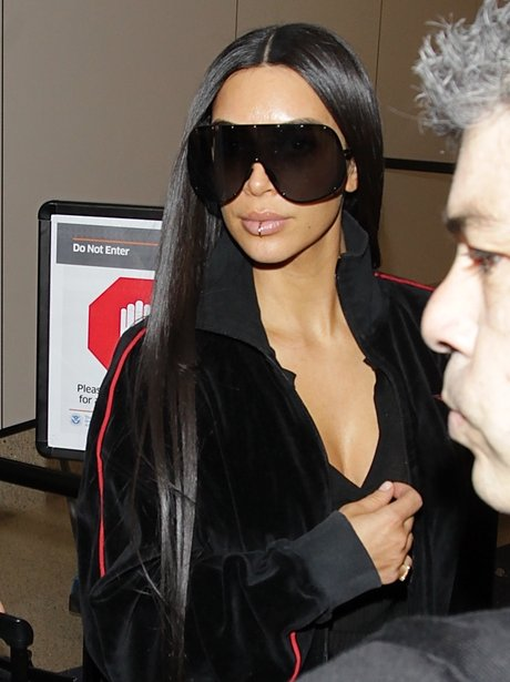 Kim Kardashian wears a lip ring as she lands into
