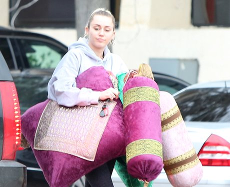 Miley Cyrus holding cushions