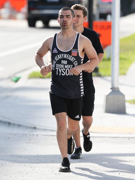 Joe Jonas shows off his muscles whilst out for a r