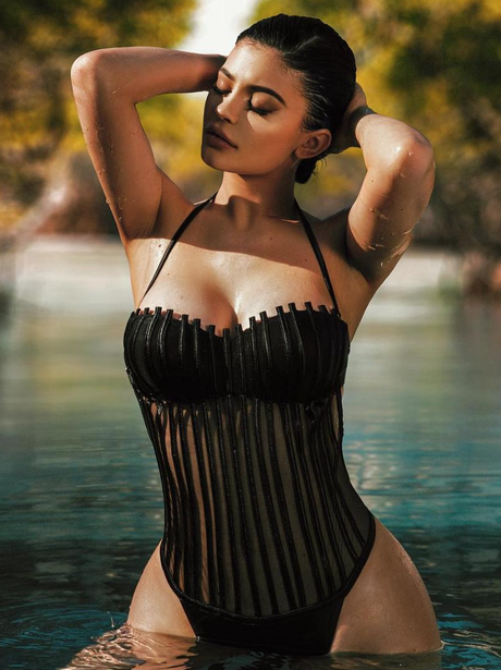 Kylie Jenner poses in a black swimsuit
