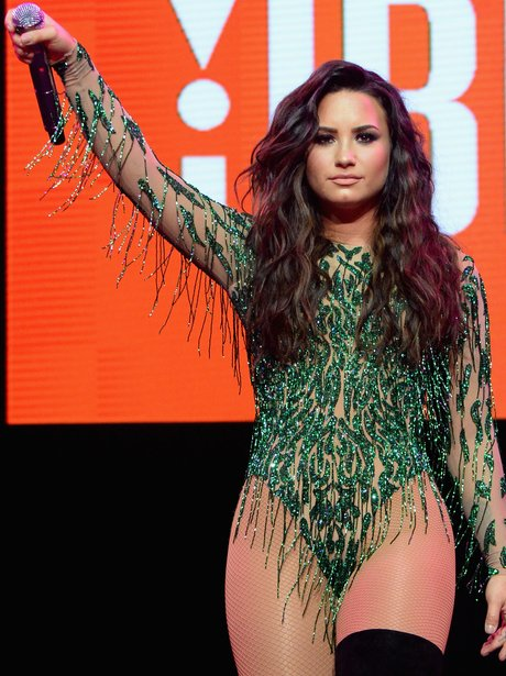 Demi Lovato wears a green sequin leotard on stage