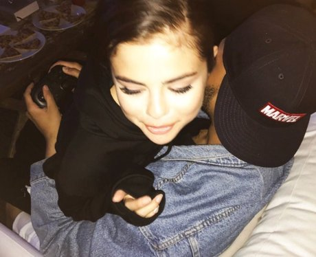 Selena Gomez cuddles The Weeknd whilst he plays vi